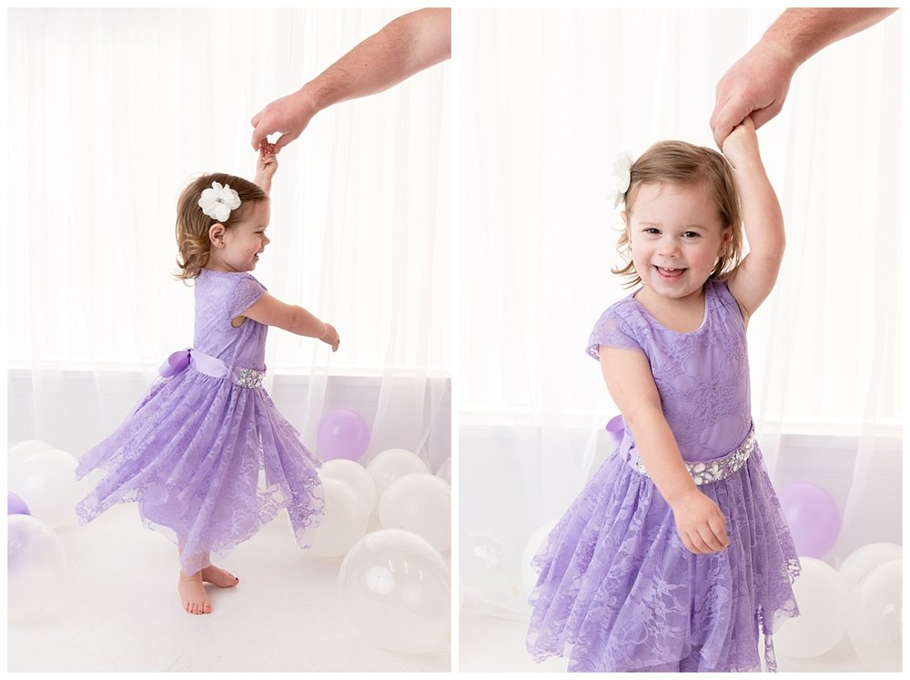 st-louis-birthday-photographer-three-year-old-girl-twirling-with-dads-hand-in-purple-dress.jpg