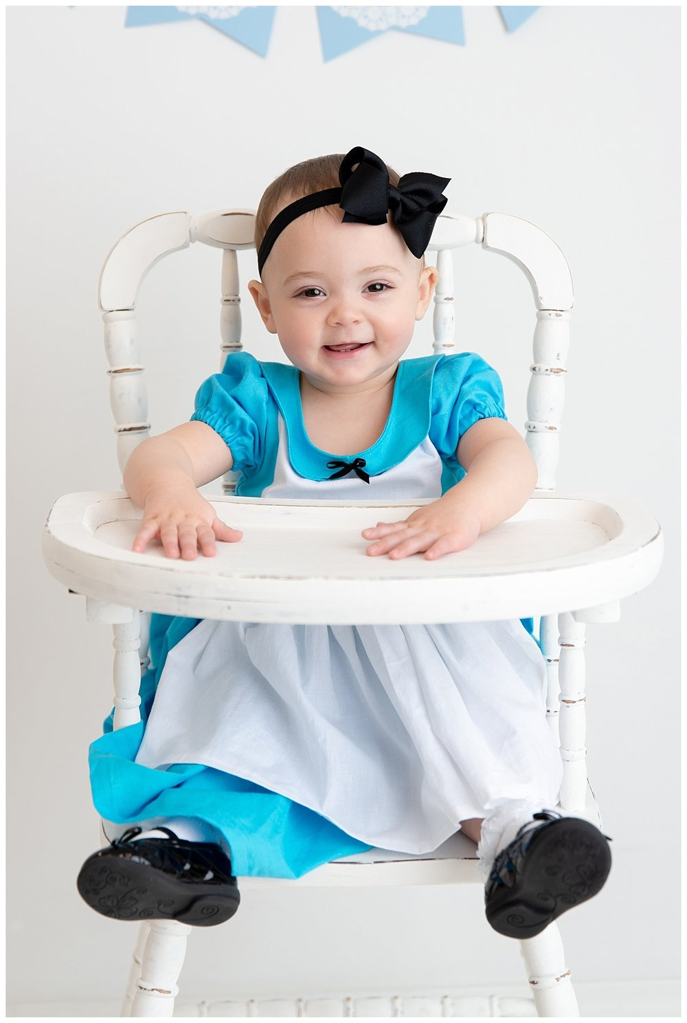 st-louis-birthday-photographer-alice-in-wonderland-dress-baby-girl-sitting-in-white-highchair.jpg