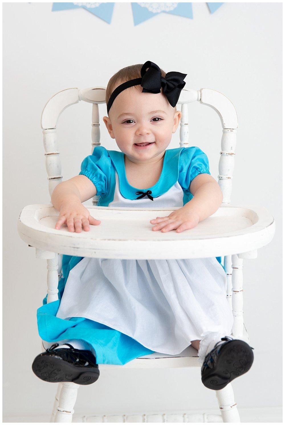st-louis-birthday-photographer-alice-in-wonderland-dress-baby-girl-sitting-in-white-highchair.jpg