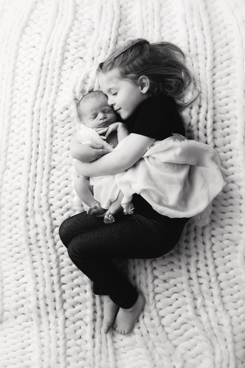 st-louis-newborn-photographer-big-sister-holding-baby-brother-view-from-above-in-black-and-white.jpg