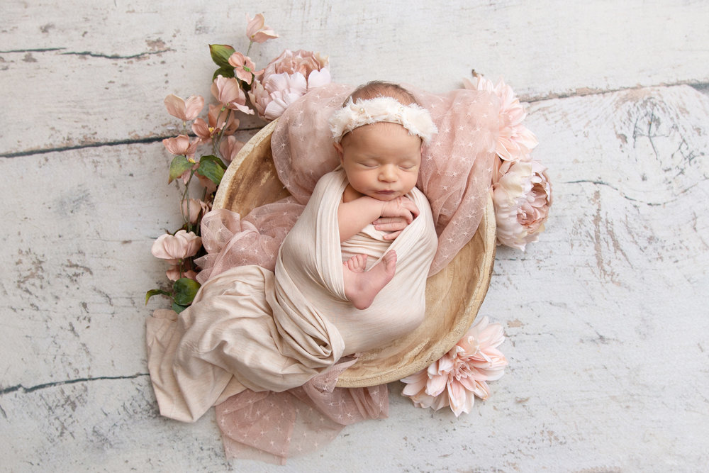 st-louis-newborn-photographer-baby-girl-wrapped-in-soft-pink-in-wood-bowl-with-pink-flowers.jpg