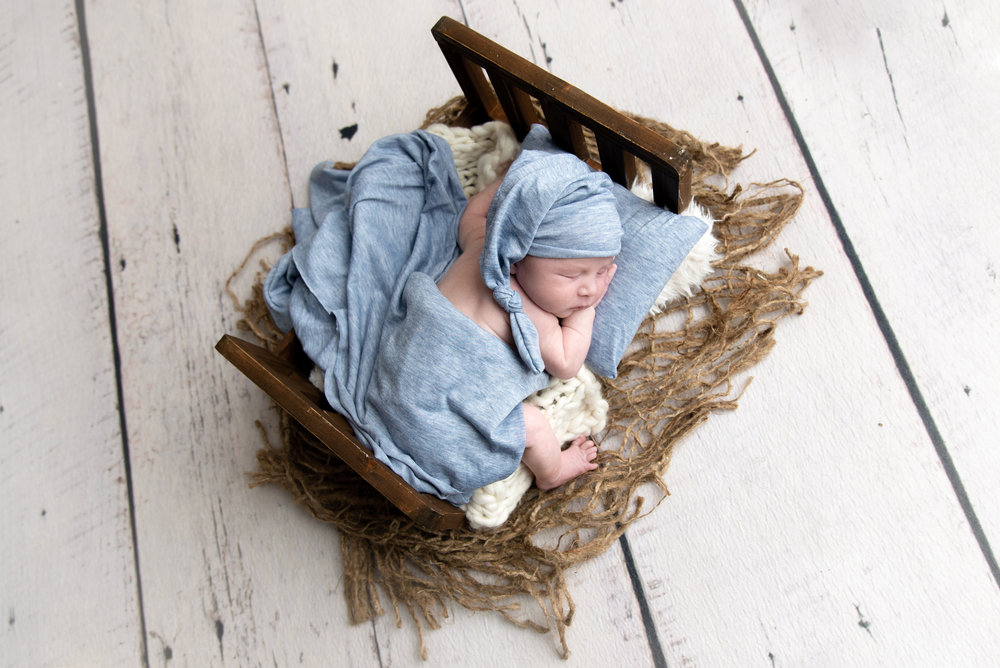 st-louis-newborn-photographer-baby-boy-in-wood-bed-with-baby-blue-hat-wrap-and-pillow.jpg
