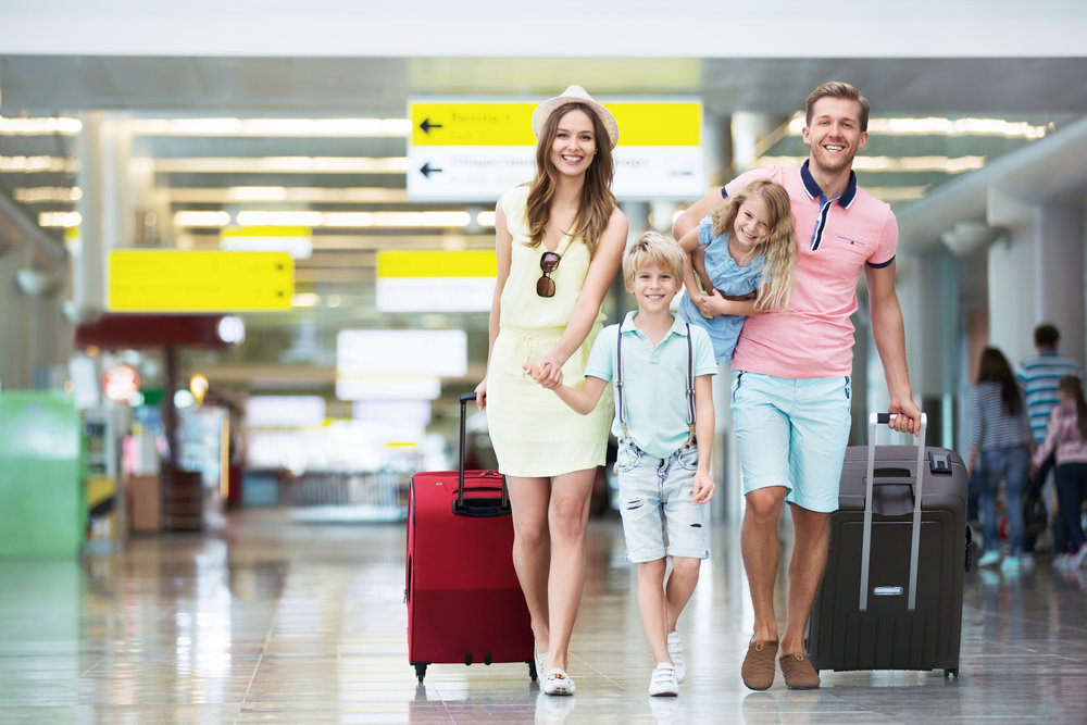 This is a happy family looking carefree at an airport. This image is a lie, and something that has never happened in the entire history of airports.