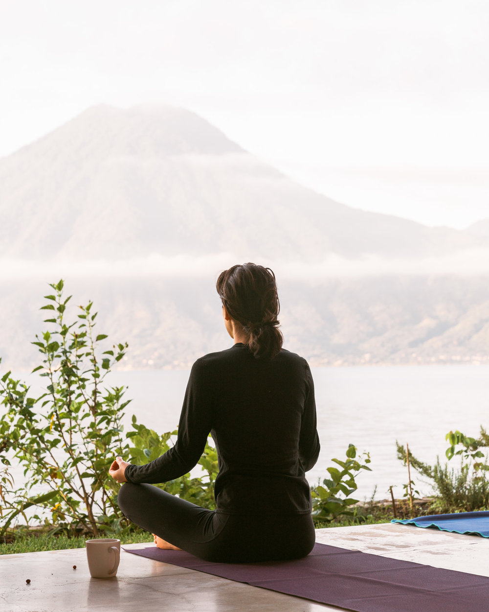 Woman meditating in front of the water at lake atitlan