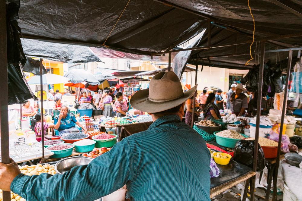 man selling goods at the sunday market at lake atitlan
