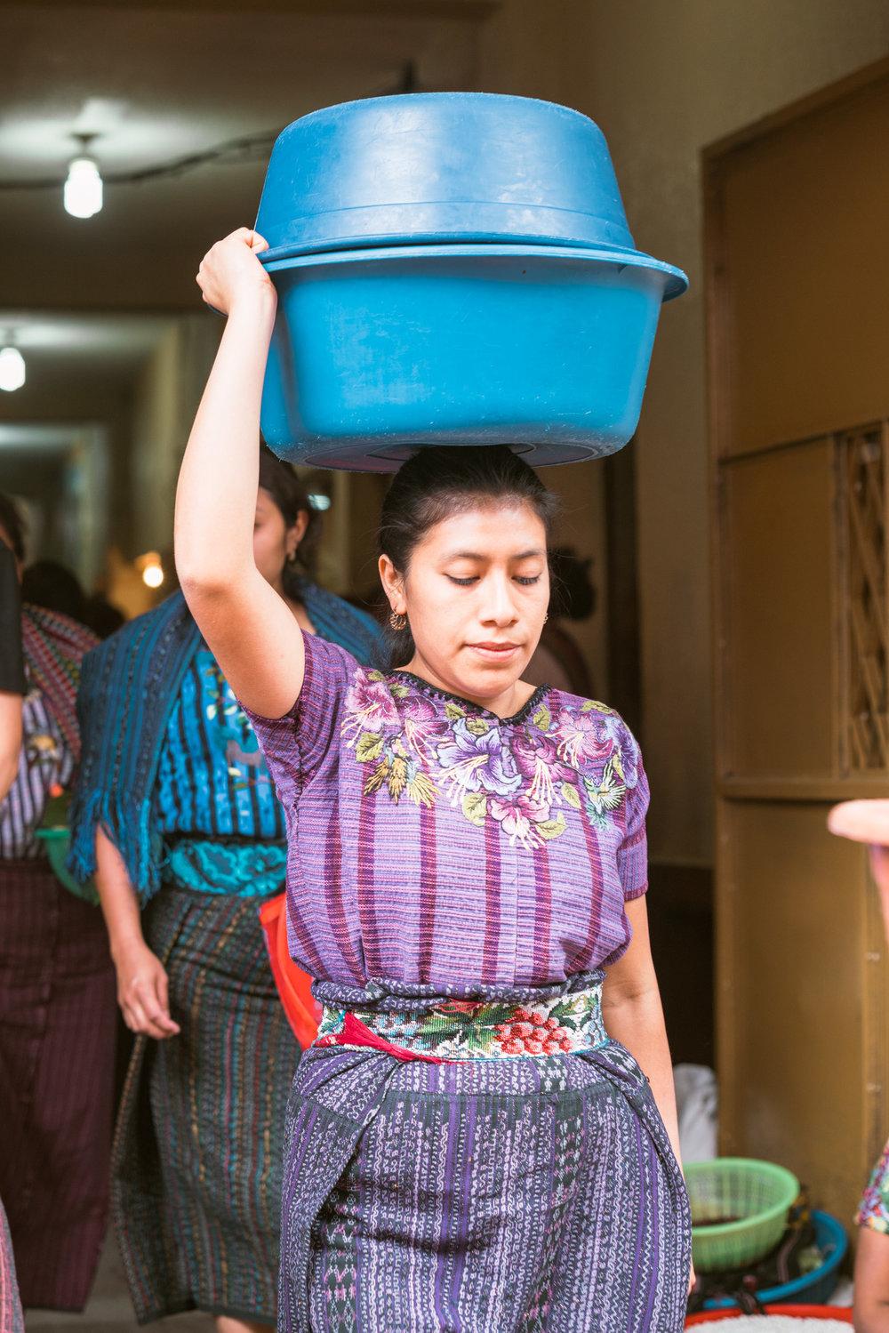 woman carrying fresh food on her at head at the sunday market at lake atitlan