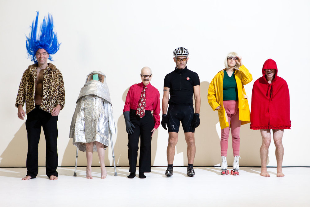 Performers Herrmann, Cunningham, Markland, Curtis, Scaroni, and Müller line up against white wall in silly costumes. (photo: Sven Hagolani)
