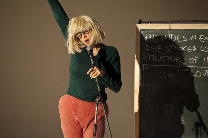 Scaroni rocks out on the microphone, in blonde wig and lumpy pink pants, next to a chalkboard. (photo: Sven Hagolani)