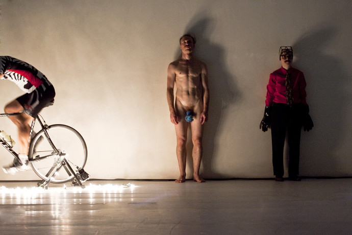 Curtis in cyclist garb pedals a bike. Müller and Markland stand neutral against a white wall. (photo: Sven Hagolani)
