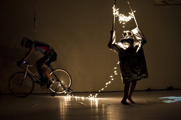 Cunningham, in silver hazmat suit, suspends string lights in the air using crutches. Curtis on bike in background. (photo: Sven Hagolani)