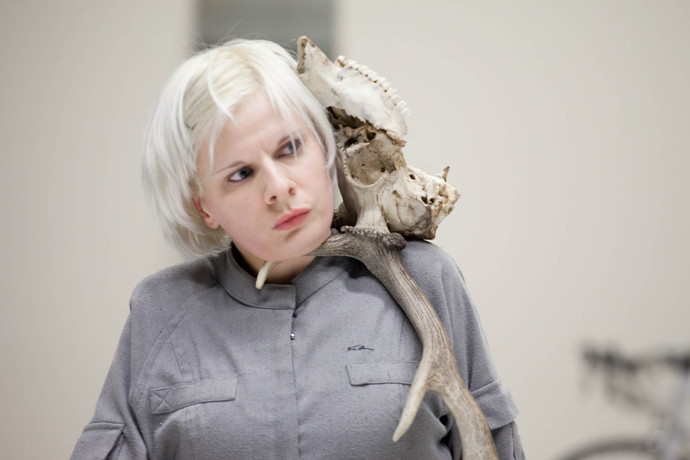 Cunningham, with silver hair and coat, balances a deer skull and antlers between her head and shoulder. (photo: Sven Hagolani)