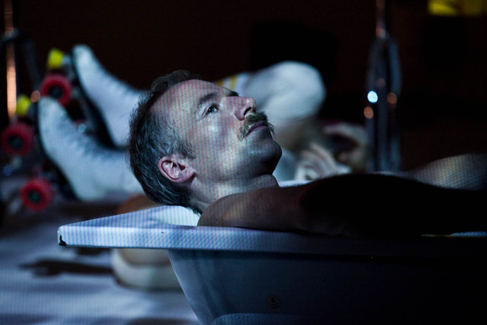 Close-up of Müller in bath tub, under dim projected light, with roller skates in the background. (photo: Sven Hagolani)