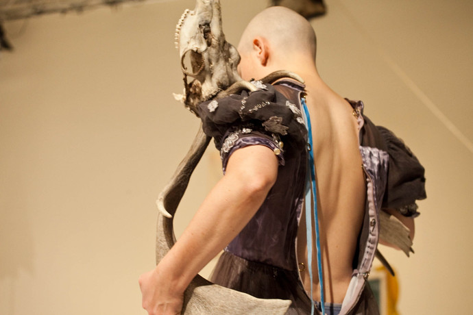 Back shot of bald male in unzipped puffed-sleeve dress and elk skull balanced on shoulder. (photo: Sven Hagolani)