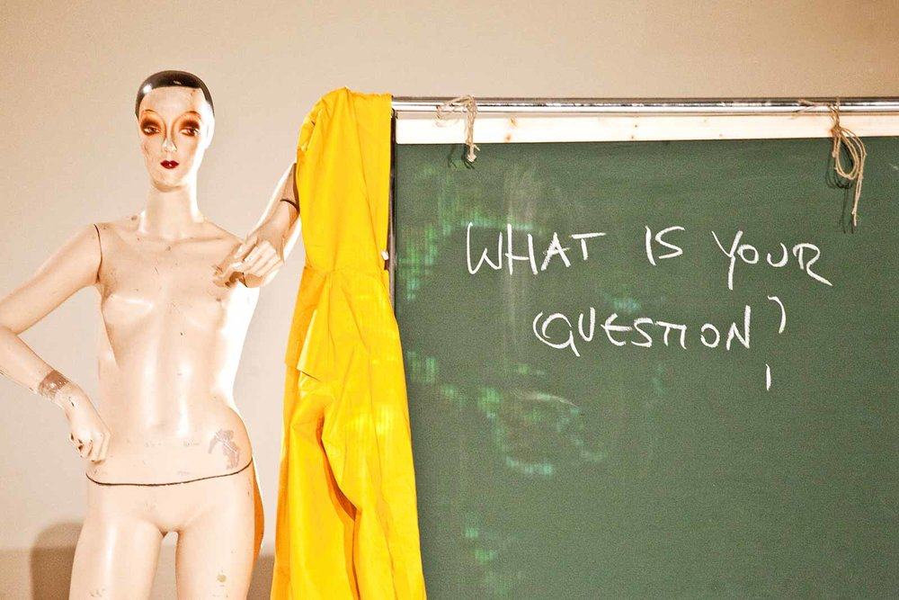 "Vintage mannequin leans jauntily against chalkboard on which is written: ""What is your Question?"" (photo: Sven Hagolani)"