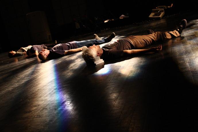 Maria Scaroni, David Toole, Jörg Müller, Jess Curtis lie on dark floor in dappled lighting; Curtis' head on book stack. (photo: Kristine Slipson)