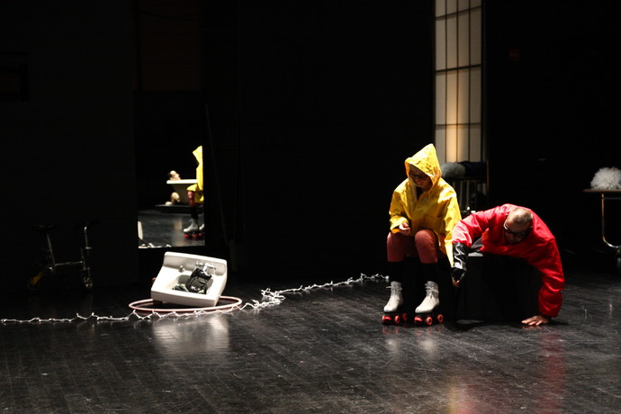Scaroni in yellow rain slicker & roller skates, and Markland, in red jacket & glasses; sink and string lights strewn on floor. (photo: Kristine Slipson)
