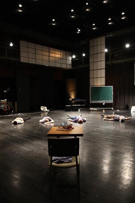 Scaroni, Toole, Müller, Curtis lie on dark floor. Vintage wood school desk in foreground; freestanding chalkboard in background. (photo: Kristine Slipson)