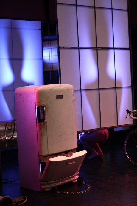 2 human torso shadows on stage walls behind a vintage refrigerator in magenta lighting. (photo: Kristine Slipson)