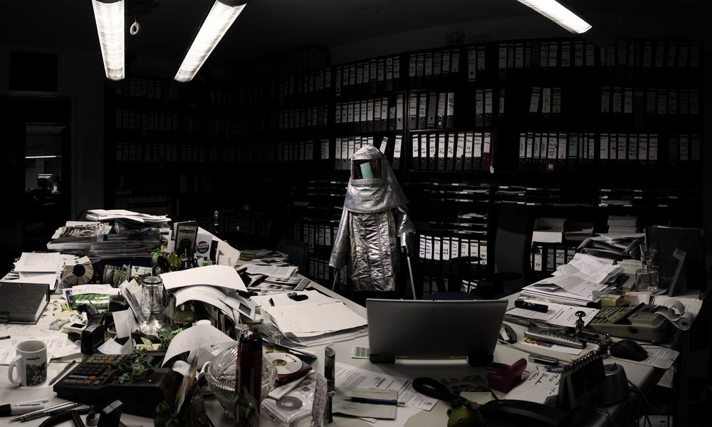 Cunningham, in oversized silver hazmat suit, is dwarfed by a cluttered office and rows of black binders. (photo: Sven Hagolani)