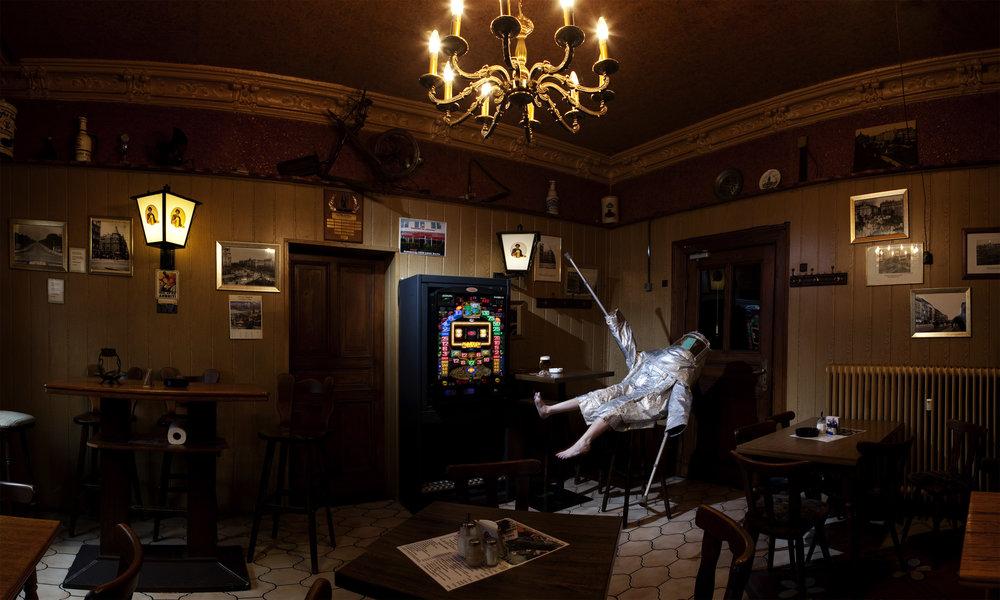 Cunningham, in silver hazmat suit, perches on barstool in dark, moody, old-school Berlin bar. (photo: Sven Hagolani)