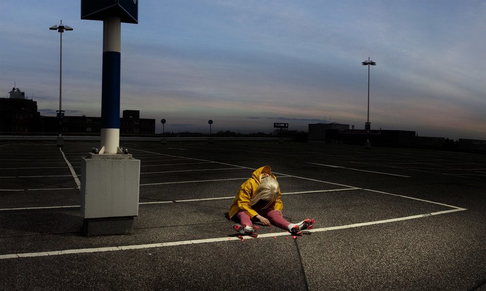 Scaroni, in blonde wig, yellow rain slicker, and skates, sits slumped in an empty parking lot at dusk. (photo: Sven Hagolani)