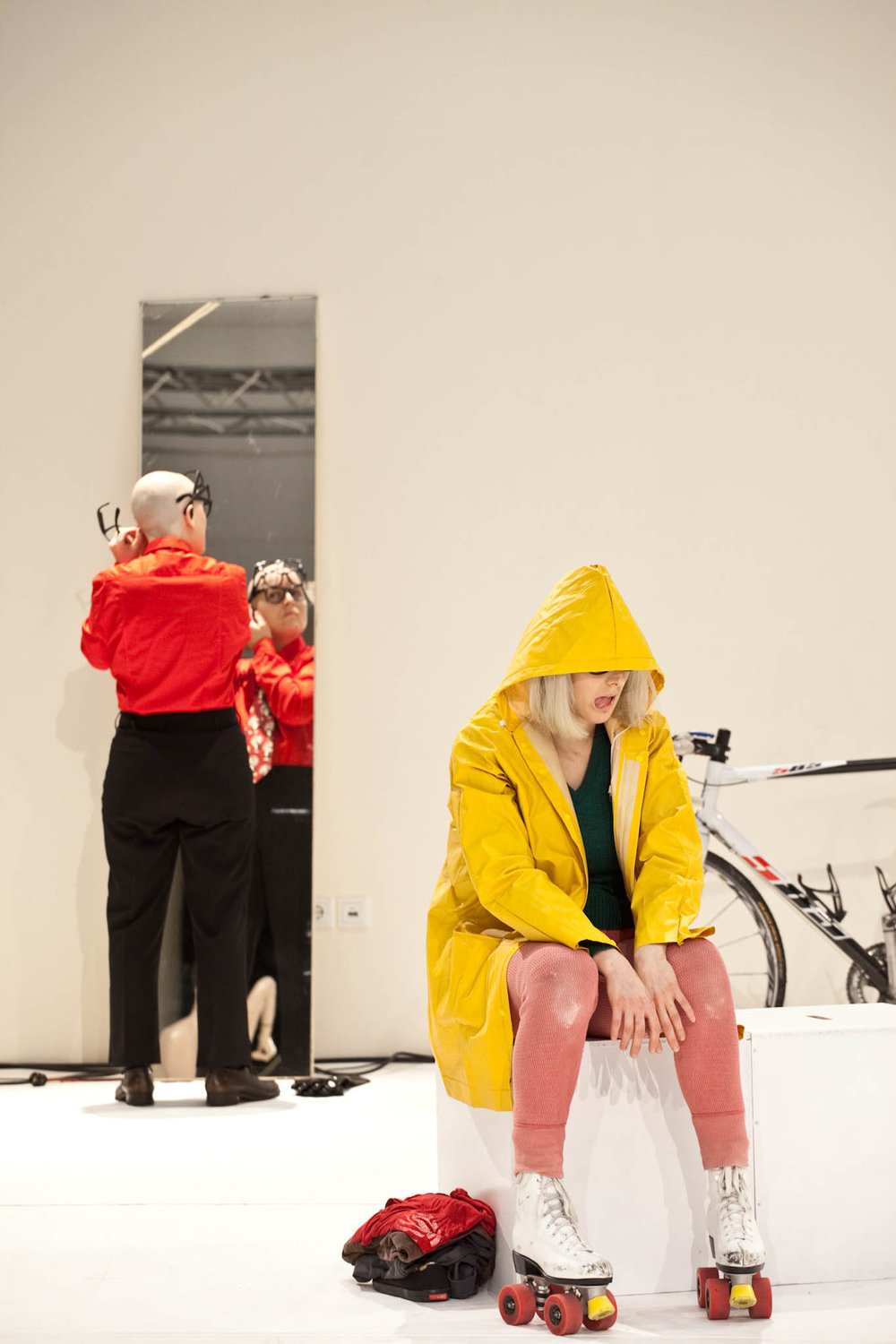 Scaroni, in wig, slicker, and skates, sits slumped, mouth agape. In background, Markland adjusts glasses in mirror. (photo: Sven Hagolani)
