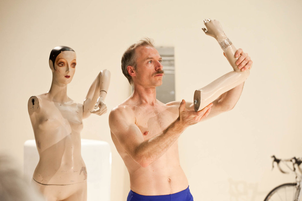 Müller, torso bare and mustachioed, holds a mannequin arm aloft. Behind him, the mannequin with arm missing. (photo: Sven Hagolani)