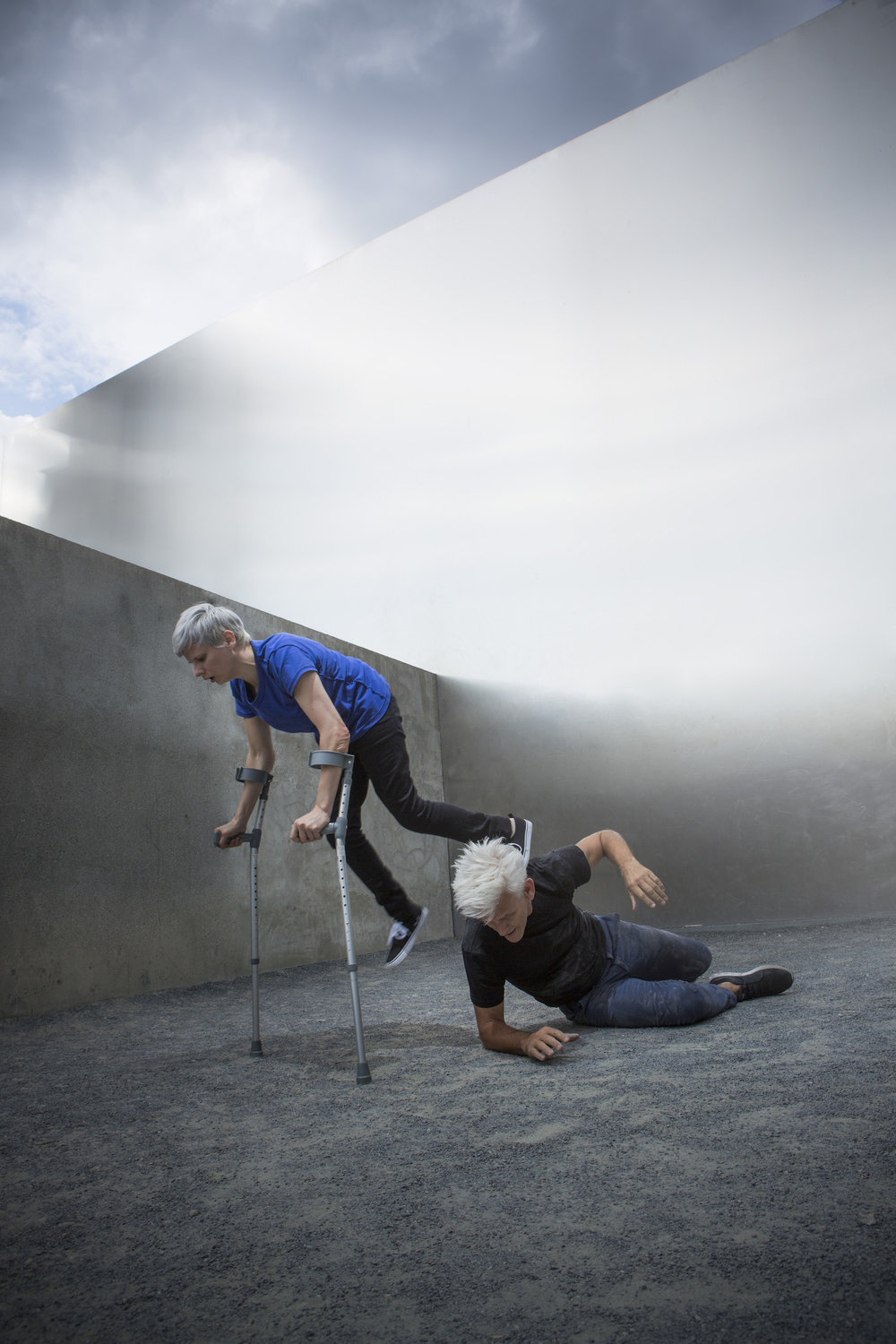 Cunningham (slight with silver hair and blue tee) balances on crutches with 1 foot on neck of Curtis, who lies on gravel ground against cement walls. (photo: Sven Hagolani)