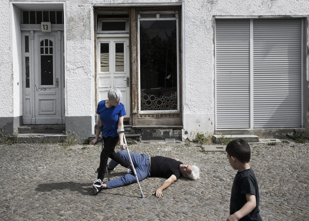 Curtis (silver haired, in black tee & jeans) lies twisted on cobblestone street. Cunningham stands on his left leg. A boy watches. (photo: Sven Hagolani)