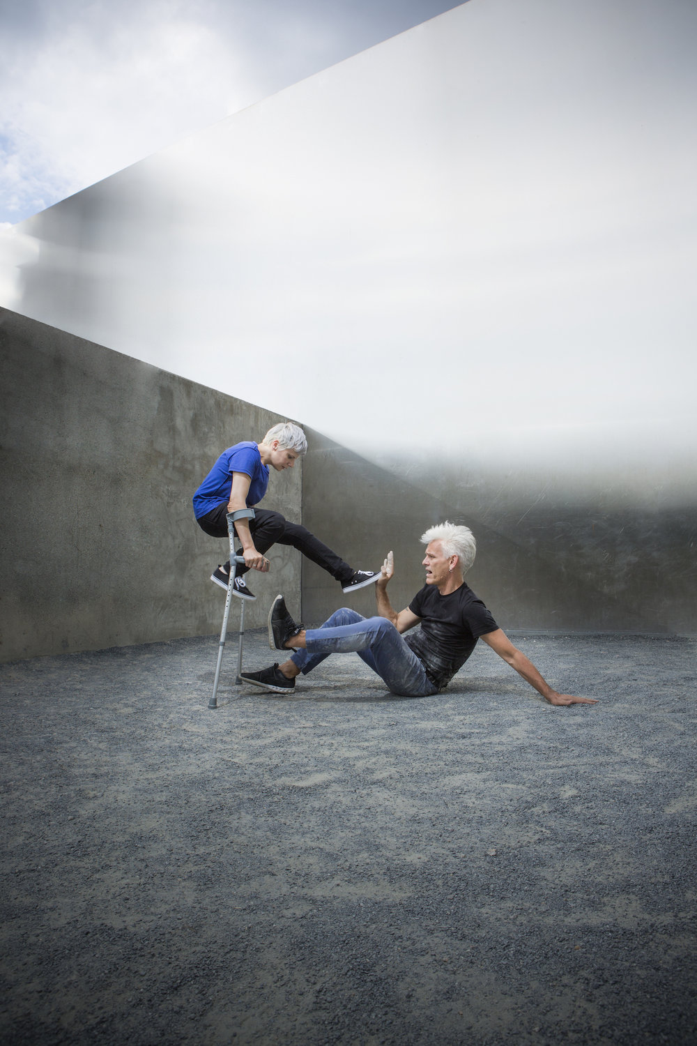 Spare, cement-walled outdoor space under blue sky. Cunningham balances between crutches, presses one foot against Curtis' hand. Curtis sits. (photo: Sven Hagolani)