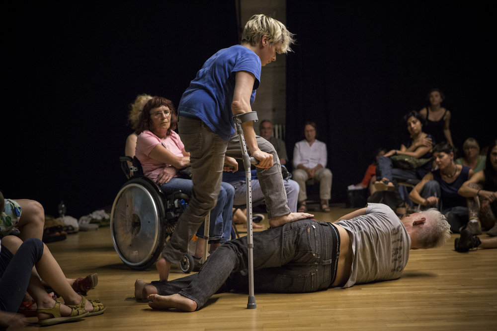 Informal performance space. Curtis lies on wood floor amid clusters of audience. Cunningham (above) places foot on his hip. (photo: Sven Hagolani)