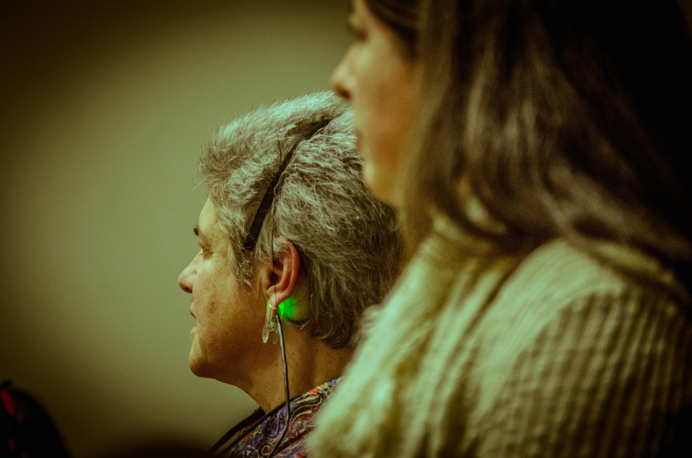 Closeup of gray-haired female audience member in headset with green light clamped to her earlobe. Another woman in foreground. (photo: Robbie Sweeny)