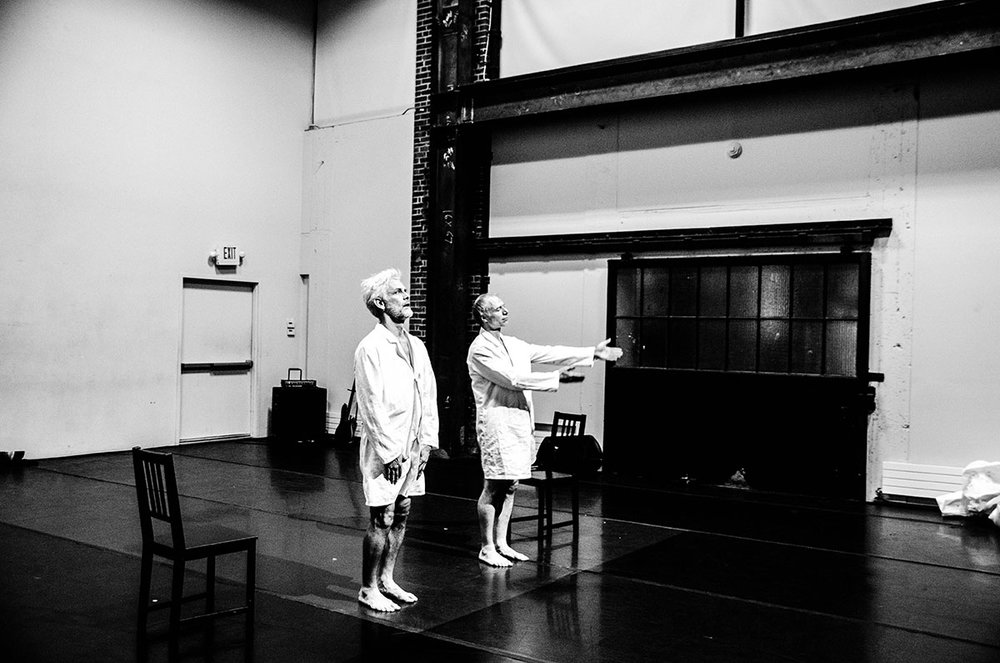 Curtis and Müller, wearing only white lab coats, stand before the audience. Müller extends arms toward audience. (photo: Robbie Sweeny)
