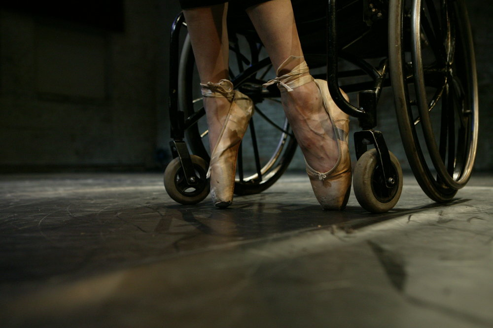 Closeup of 2 feet in ballet pointe shoes, between the wheels of a wheelchair on black marley floor. (photo: Sven Hagolani)