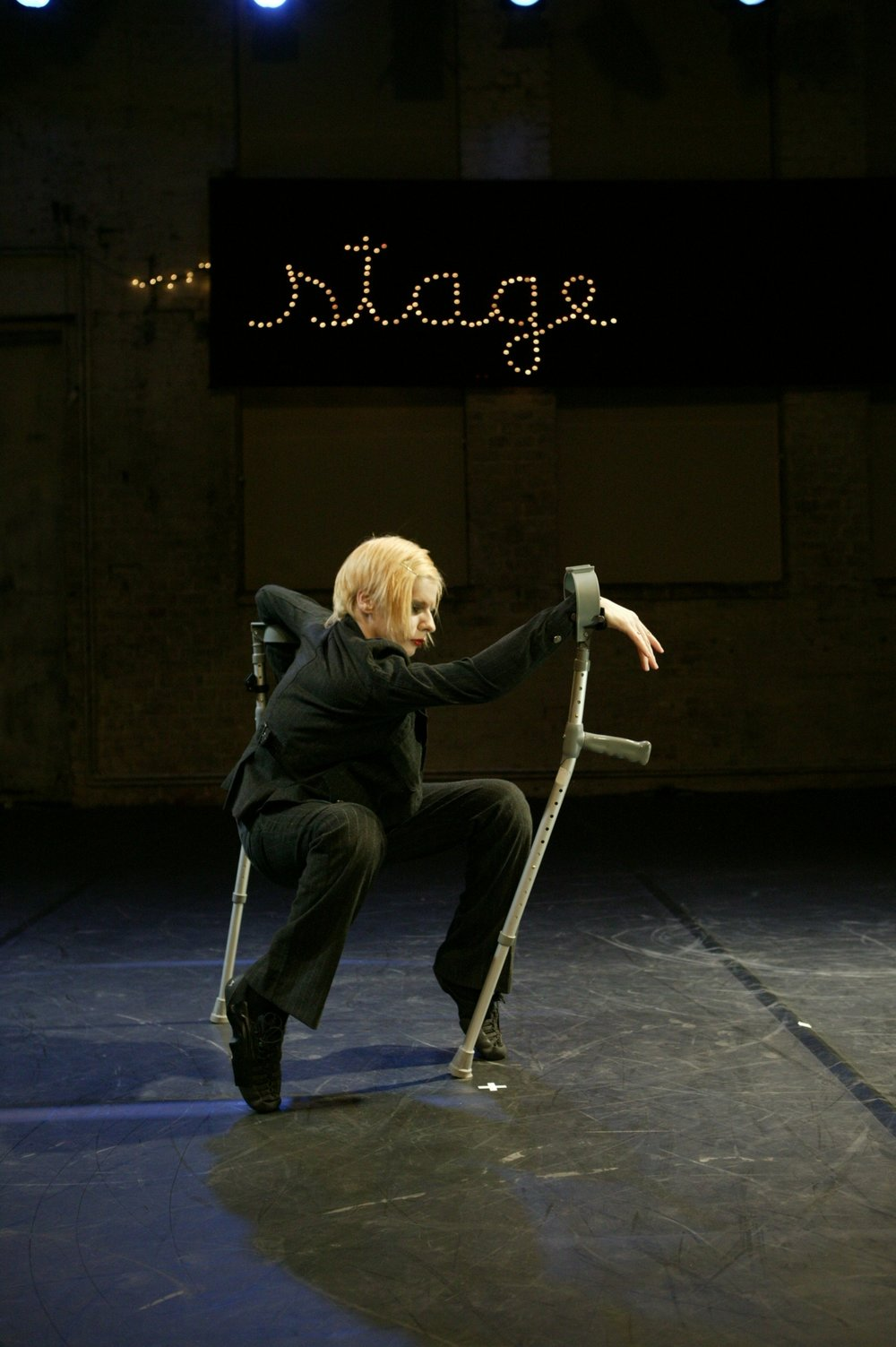 "Cunningham, blonde in black suit, squats on tiptoes supported at wrists by 2 crutches. Lights above her head spell ""stage"". (photo: Sven Hagolani)"
