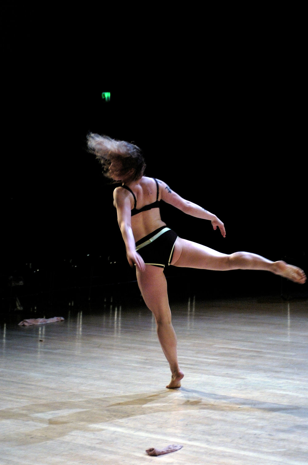 Leah Martini dances on wooden floor in bikini: back leg outstretched, hair flying, arms stretched behind her. (photo: Andy Mogg)