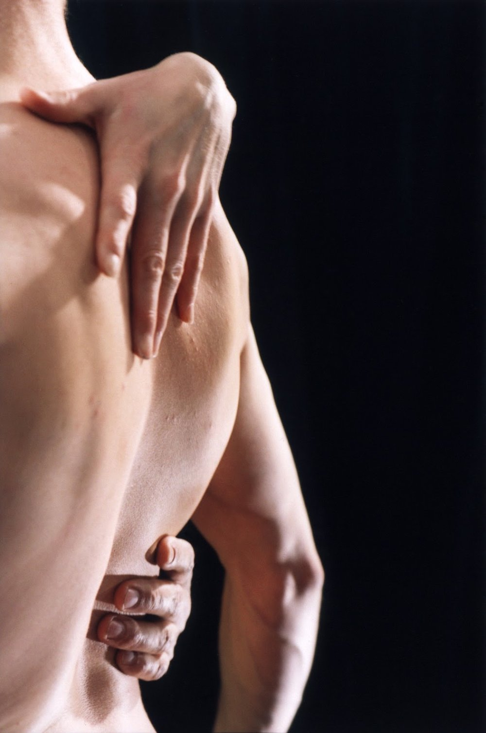 Closeup of nude back with hands at waist and upper back, against black background. (photo: Andy Mogg)