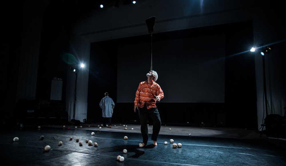 Curtis (in wild red patterned shirt) balances a broom on his forehead, surrounded by dozens of baseballs littering the black stage floor. (photo: Robbie Sweeny)