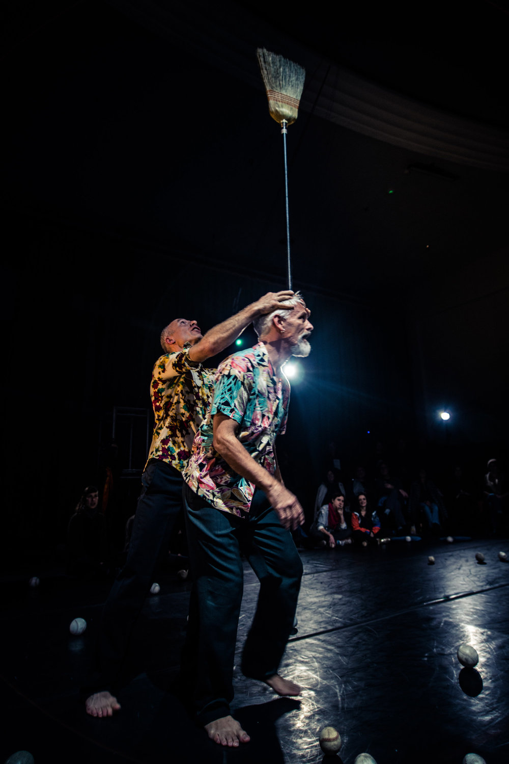 Müller and Curtis, barefoot in wildly patterned short sleeve shirts, balance a broom atop Curtis' head. Audience watches. (photo: Robbie Sweeny)
