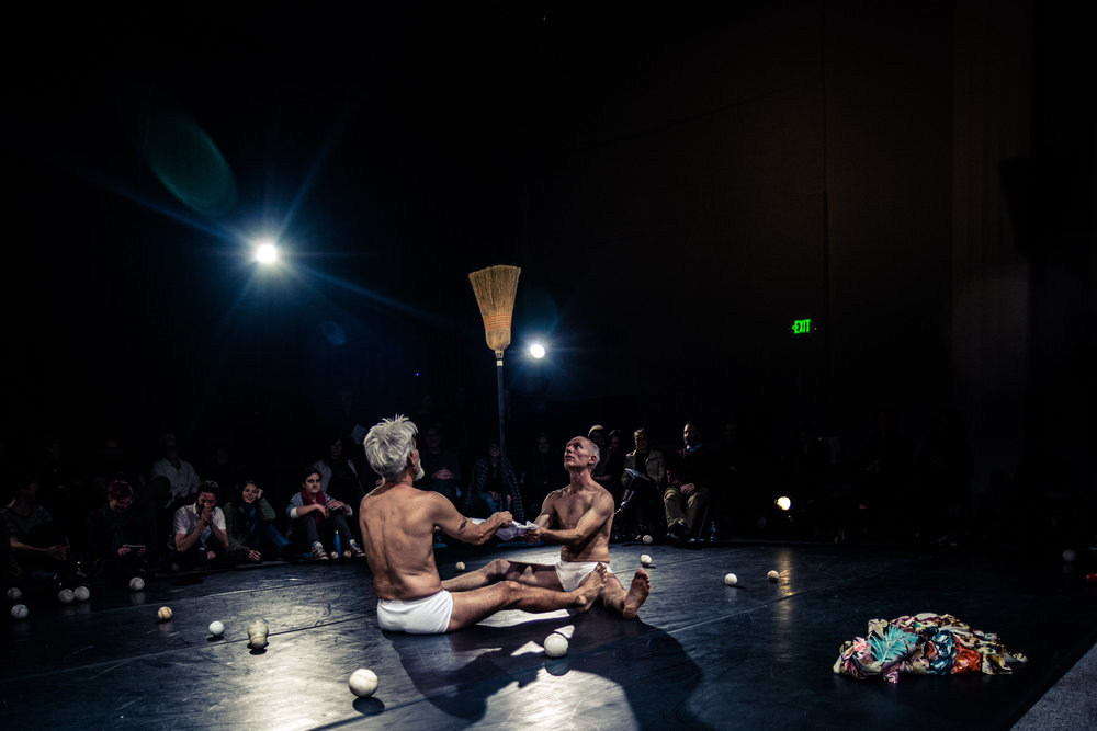 Curtis and Müller, in white underwear, sit facing one another holding a small piece of fabric on which they balance a broom. (photo: Robbie Sweeny)