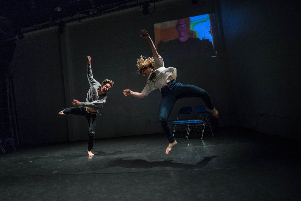 Anderson and Crain mid-air, mirroring one another in sideways leaps. Image of Curtis projected on wall behind (as from Skype). (photo: Robbie Sweeny)