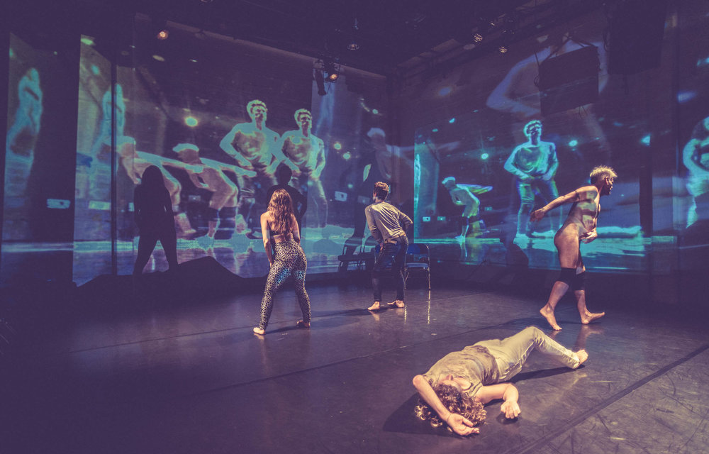 The cast is surrounded by projections of themselves on 2 walls of performance space. Crain lies in the foreground. (photo: Robbie Sweeny)