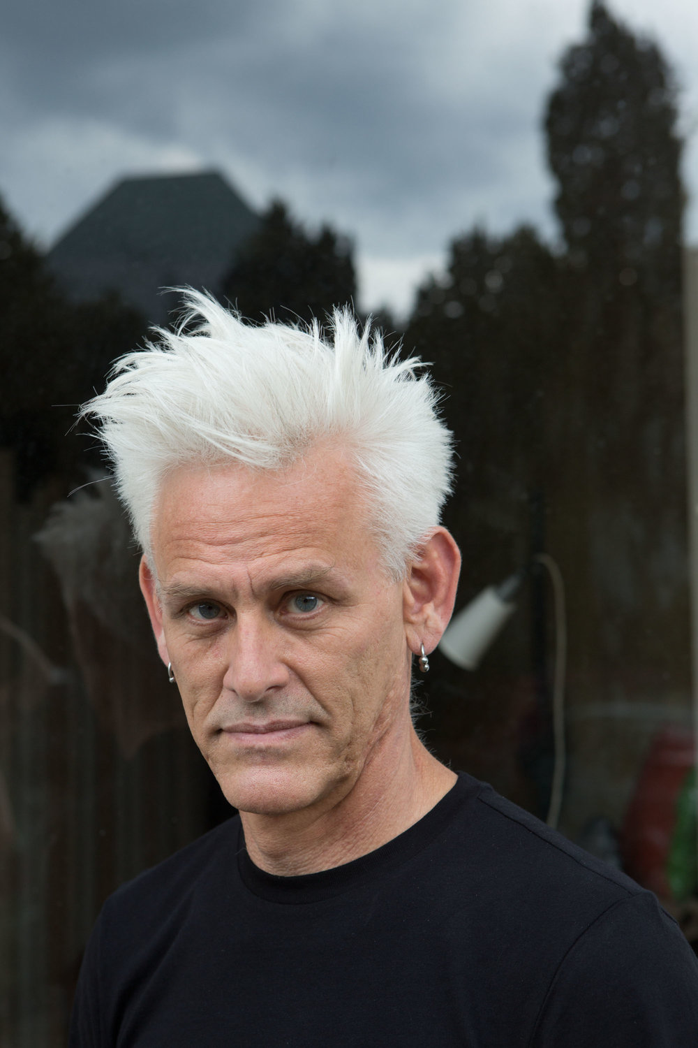 Jess Curtis wears a black tee shirt and silver earrings. He has a shock of white hair and looks into the camera. (photo: Sven Hagolani)