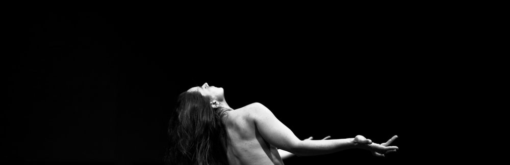 Wide horizontal image of Rachael Dichter topless in back bend against black background (photo: Robbie Sweeny)