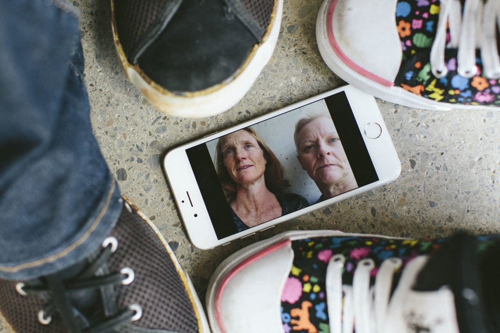 cell phone on cement between people's feet displays photo of Brandel and Fearon (photo: Emma Jervis)