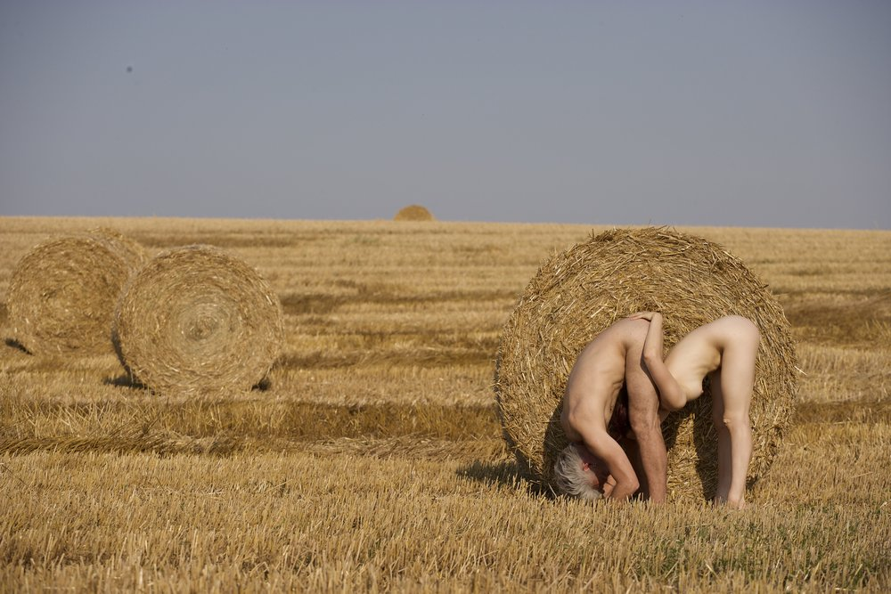 Against a round hay bale, Curtis and Scaroni in adjoining forward folds, her hands on his lower back, head between his thighs. (photo: Sven Hagolani)