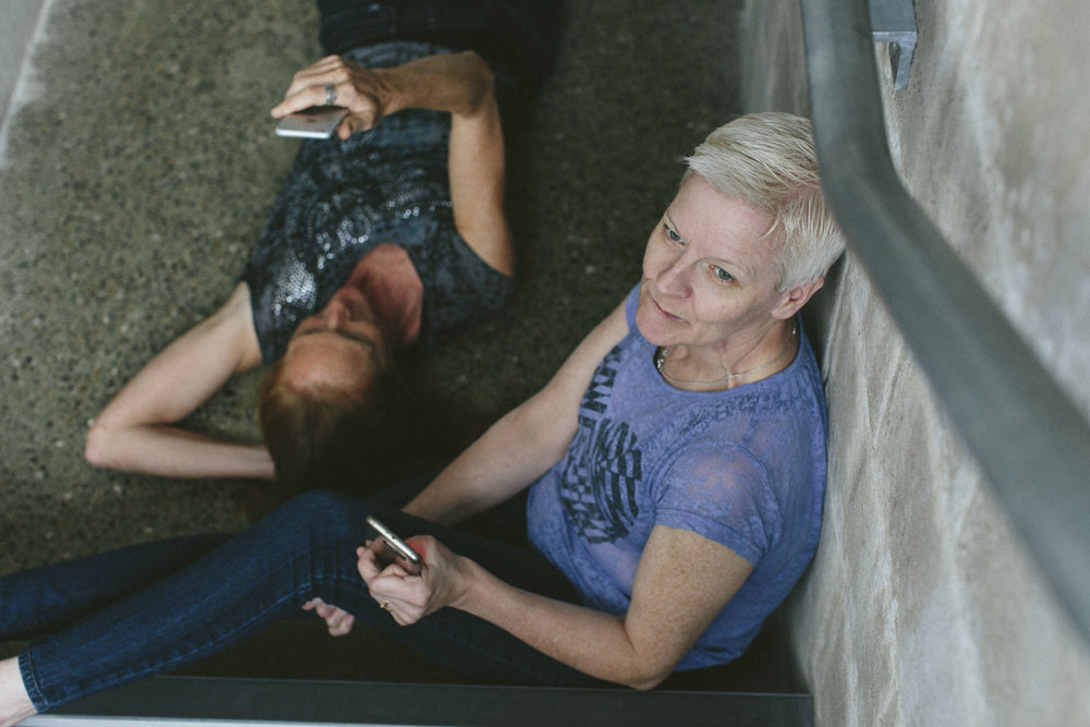Tara Brandel lies on ground and Linda Fearon sits, both hold cell phones (photo: Emma Jervis)
