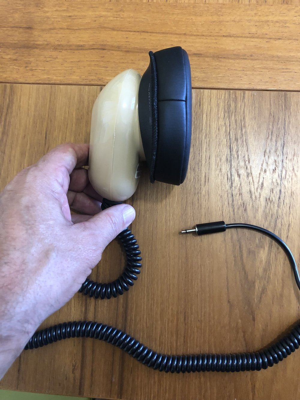 [Hand holding a stenographer's mask a mouth sized metal case with a flexible seal that fits around the mouth and contains a microphone. It is approximately the size of the hand.]