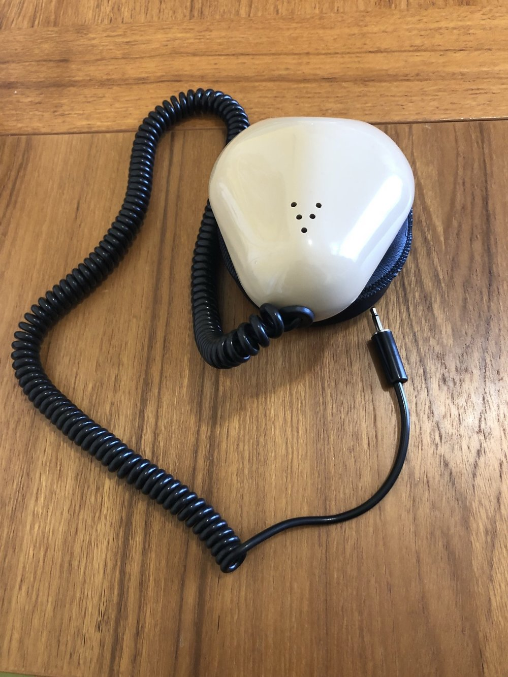 [A 'stenographer's mask' rests on a table it is a mouth sized metal case  containing a microphone with a flexible seal that fits around the mouth. A small microphone cable is attached.]