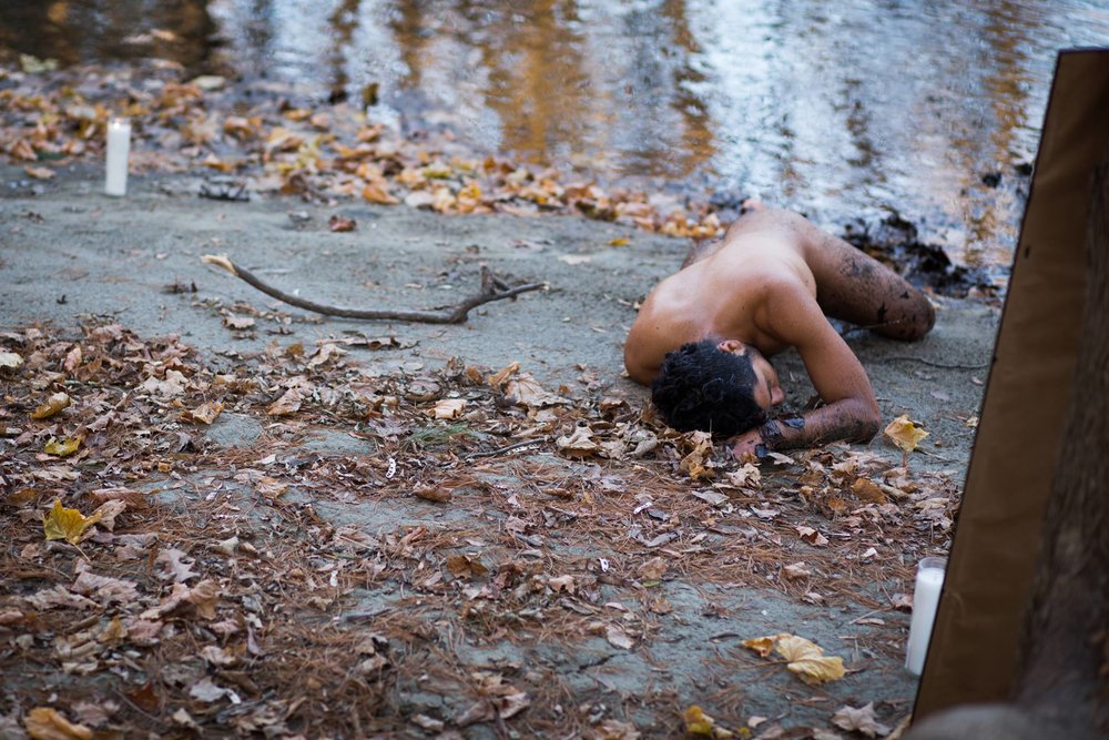 Image description: Randy Reyes is laying face down, naked on the dirt between a body of water and some leaves. There is mud on his forearm and leg and there are candles burning in the corners of the image.